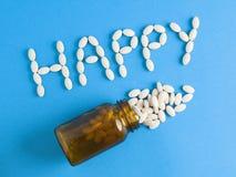 Wort glücklich und Glaspillen Lizenzfreie Stockfotos