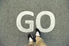 Wort GO geschrieben auf eine Asphaltstraße Draufsicht der Beine und des sho Stockfotos