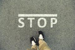 Wort-Halt geschrieben auf eine Asphaltstraße Draufsicht der Beine Lizenzfreies Stockbild