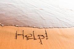 Wort HILFE auf Sand Stockfotos