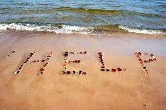 Wort HILFE auf Strandsand Stockfotos