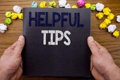 Wort, hilfreiche Tipps schreibend Geschäftskonzept für Hilfe in FAQ oder im Rat, geschrieben auf Notizblocknotizbuchbuch auf dem  Lizenzfreie Stockfotografie