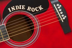 Wort-Indie Felsen mit hölzernen Buchstaben, Nahaufnahme auf einer Oberfläche der roten Akustikgitarre Musikunterhaltungshintergru lizenzfreies stockfoto