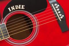 Wort Indie mit hölzernen Buchstaben, Nahaufnahme auf einer Oberfläche der roten Akustikgitarre Musikunterhaltungshintergrund lizenzfreie stockfotos