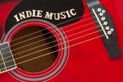 Wort-Indie Musik mit hölzernen Buchstaben, Nahaufnahme auf einer Oberfläche der roten Akustikgitarre Musikunterhaltungshintergrun stockfotografie