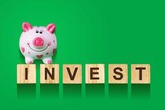 Wort investieren, bestanden aus Buchstaben auf hölzernen Bauwürfeln mit Sparschwein Grüner Hintergrund, lokalisiertes Konzeptgesc Stockfotos