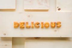 Wort-KÖSTLICHE Alphabet-Kekse auf hölzernem Hintergrund stockfotografie