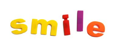 Wort LÄCHELN von magnetischen Buchstaben auf weißer, Draufsicht lizenzfreie stockbilder