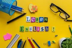 Wort LERNEN ENGLISCH, das mit geschnitztem Buchstaben onyellow Schreibtisch mit Büro oder Schulbedarf, Briefpapier gemacht wird K lizenzfreie stockfotos