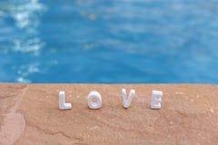 Wort-Liebe auf dem Felsen und dem Wasser Stockbilder