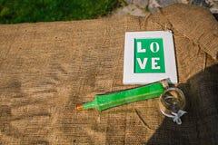 Wort-Liebe auf dem Hintergrund von Leinwand Detail einer Eleganzfarbbandblume Lizenzfreie Stockbilder