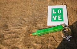 Wort-Liebe auf dem Hintergrund von Leinwand Detail einer Eleganzfarbbandblume Lizenzfreie Stockfotos