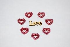 Wort-Liebe in einer Umwelt von roten Herzen Hölzerne Aufschrift Openwork Plastik der Herzen lizenzfreie stockfotos