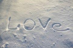 Wort LIEBE geschrieben auf den Schnee Lizenzfreie Stockfotos