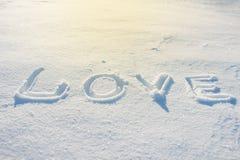 Wort LIEBE geschrieben auf den Schnee Stockbilder
