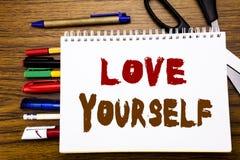 Wort, Liebe sich schreibend Geschäftskonzept für positiven Slogan für Sie geschrieben auf Notizbuch, hölzerner Hintergrund mit Bü Lizenzfreie Stockbilder
