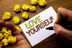 Wort, Liebe sich schreibend Konzept für positiven Slogan für Sie geschrieben auf Notizbuchbriefpapier auf dem hölzernen Hintergru Stockfotografie
