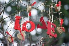 Wort-Liebe und Herz-förmige Verzierungen Stockbild