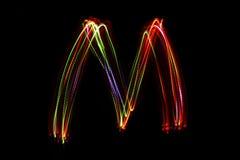 Wort ` M ` Schreiben vom Licht Lizenzfreie Stockfotos