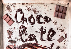 Wort mit flüssiger Schokolade auf metallischem Hintergrund Stockfotografie