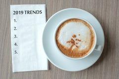 Wort mit 2019 TENDENZEN mit heißer CappuccinoKaffeetasse auf Tabellenhintergrund am Morgen Neues Jahr-neuer Anfang, Entschließung lizenzfreie stockbilder