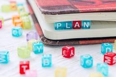 Wort PLAN geschrieben auf einen farbigen Block in ein Buch Stockbild