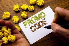 Wort, Promo-Code schreibend Konzept für Förderung für das on-line-Geschäft geschrieben auf Notizbuchbriefpapier auf dem hölzernen Stockbild