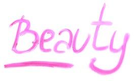 Wort SCHÖNHEIT geschrieben mit Lippenstift auf weißen Hintergrund Augenschminken der verschiedenen Farben stockfotos