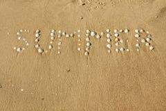 Wort Sommer ausgebreitete Seashells auf dem Sand lizenzfreie stockfotos