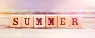 Wort-Sommer mit hölzernen Würfeln auf Tabelle Stockbild
