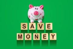 Wort sparen das Geld, bestanden aus Buchstaben auf hölzernen Bauwürfeln mit Sparschwein Grüner Hintergrund, lokalisiertes Konzept Stockbilder