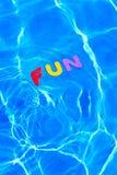Wort SPASS, der in einen Swimmingpool schwimmt Lizenzfreie Stockfotografie