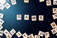 Wort SPIEL mit hölzernen Buchstaben auf schwarzem Brett mit Würfeln und Buchstaben im Kreis Stockfotos