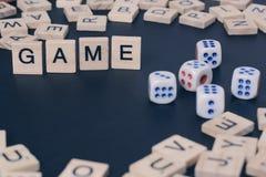 Wort SPIEL mit hölzernen Buchstaben auf schwarzem Brett mit Würfeln und Buchstaben im Kreis Lizenzfreies Stockfoto