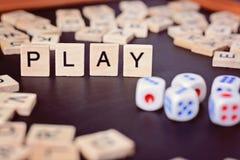Wort SPIEL mit hölzernen Buchstaben auf schwarzem Brett mit Würfeln und Buchstaben im Kreis Lizenzfreie Stockfotografie