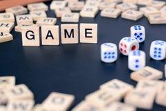 Wort SPIEL mit hölzernen Buchstaben auf schwarzem Brett mit Würfeln und Buchstaben im Kreis Stockfotografie