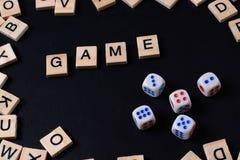 Wort SPIEL mit hölzernen Buchstaben auf schwarzem Brett mit Würfeln und lette Lizenzfreies Stockfoto