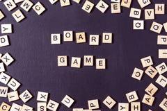 Wort SPIEL mit hölzernen Buchstaben auf schwarzem Brett mit Würfeln und lette Stockfoto