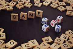 Wort SPIEL mit hölzernen Buchstaben auf schwarzem Brett mit Würfeln und lette Stockbilder
