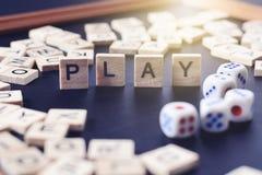 Wort SPIEL mit hölzernen Buchstaben auf schwarzem Brett mit Würfeln und lette Lizenzfreie Stockfotografie