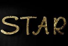Wort ` Stern `, das aus Gold heraus geschaffen wurde, spiegelte Buchstaben wider Lizenzfreie Stockfotografie