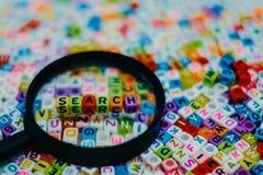 Wort ` SUCHE-` auf der Lupe lizenzfreie stockfotografie