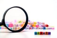 Wort ` SUCHE-` auf der Lupe mit Alphabetbuchstaben bördelt Hintergrund stockfotos