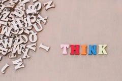 Wort THINK machte mit h?lzernen Buchstaben des Blockes nahe bei einem Stapel anderer Buchstaben lizenzfreies stockbild