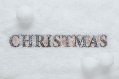 Wort-Weihnachten im Schnee mit Schneebällen Stockbild