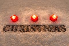Wort-Weihnachten mit Schnee und Kerzen Stockfotos