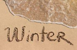 Wort-Winter ist die Hand, die auf Sand geschrieben wird Lizenzfreie Stockfotografie