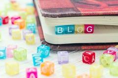 Wortblog geschrieben auf einen farbigen Block in ein Buch auf Tabelle Stockfoto