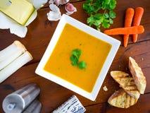 Wortel en koriandersoep met ingrediënten Stock Fotografie