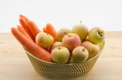 Wortelen en appelen in een mand Stock Foto's